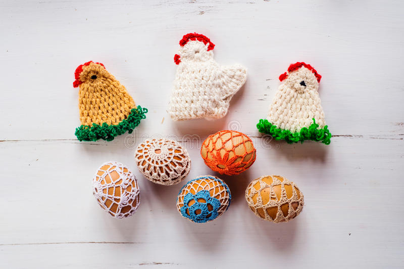 Poulets et oeufs à crochet colorés de Pâques contre le backg en bois photographie stock libre de droits