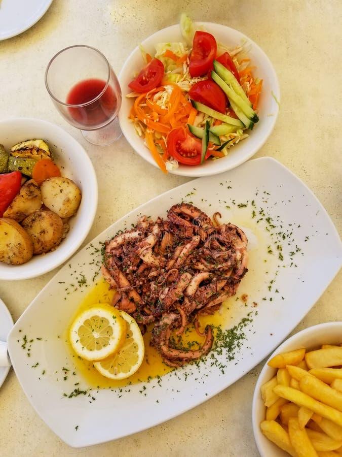 Poulpe frit avec le citron et les épices, les légumes et les pommes frites du plat blanc avec le verre de vin rouge photos stock