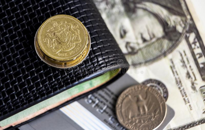 Pound coin, old dollar coin and banknote with wallet on the table. The concept of the main currency exchange can be used worldwide.  stock photos