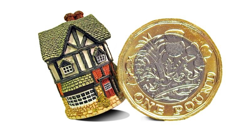 Pound gold coin toppling home property mortgage unstable house finance stock photo