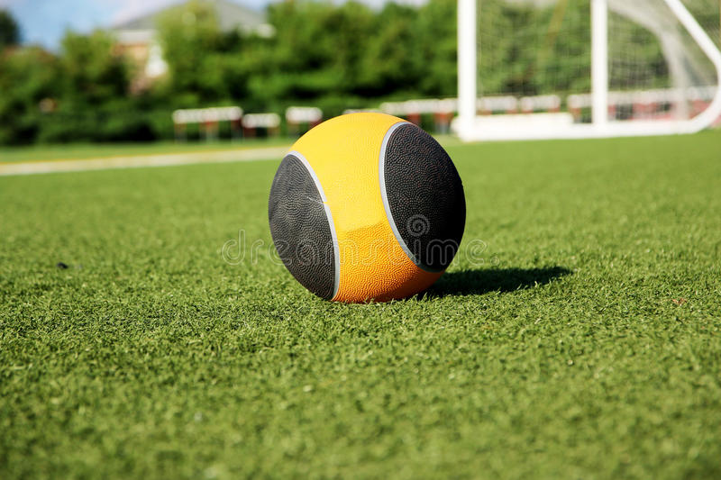 10 pound medicine ball on a green turf field. A med ball sits on a green turf field stock images