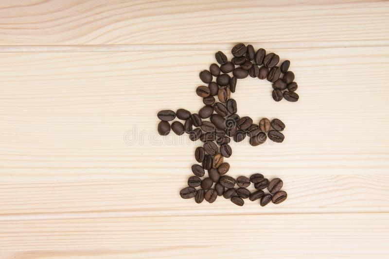Pound sign. A sign denoting an English pound which is composed of roasted coffee beans. Grains lie on a wooden textured countertop in light colors royalty free stock images