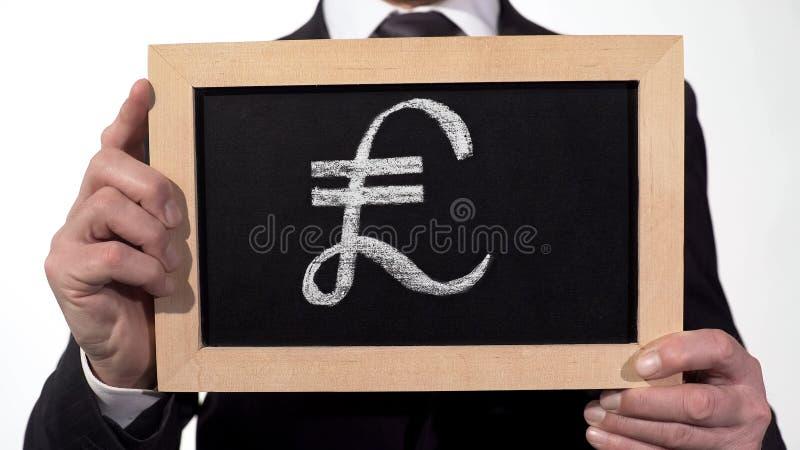 Pound symbol drawn on blackboard in businessman hands, British currency, finance stock photos