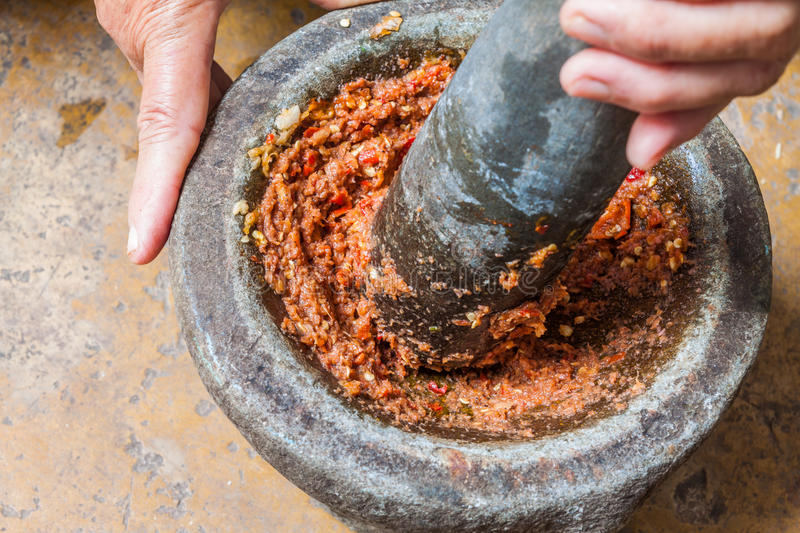 Pounding Thai chili sauce. In stone mortar with pestle royalty free stock photography