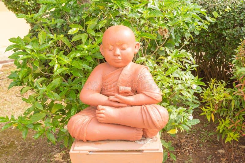 Poupée d'argile de novice bouddhiste tenant se reposer pour la méditation photo stock