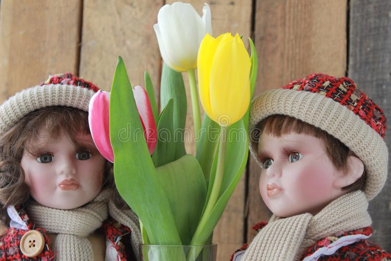Poupée dans une robe rouge et des tulipes photos stock