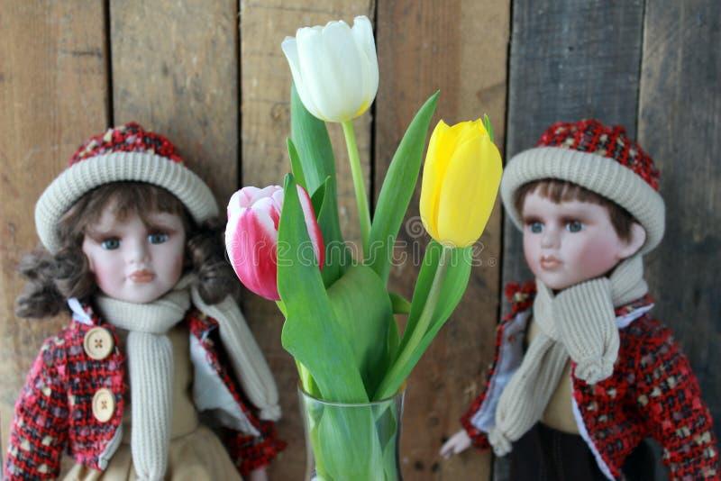 Poupée dans une robe rouge et des tulipes image libre de droits