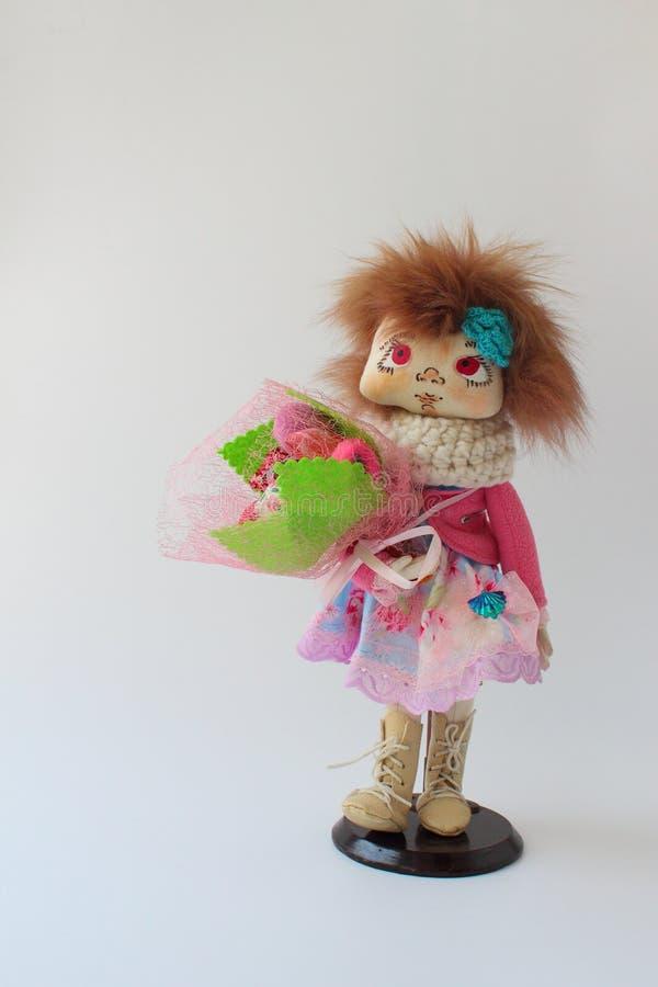 Poupée de textile dans une veste rose avec un bouquet des fleurs photographie stock