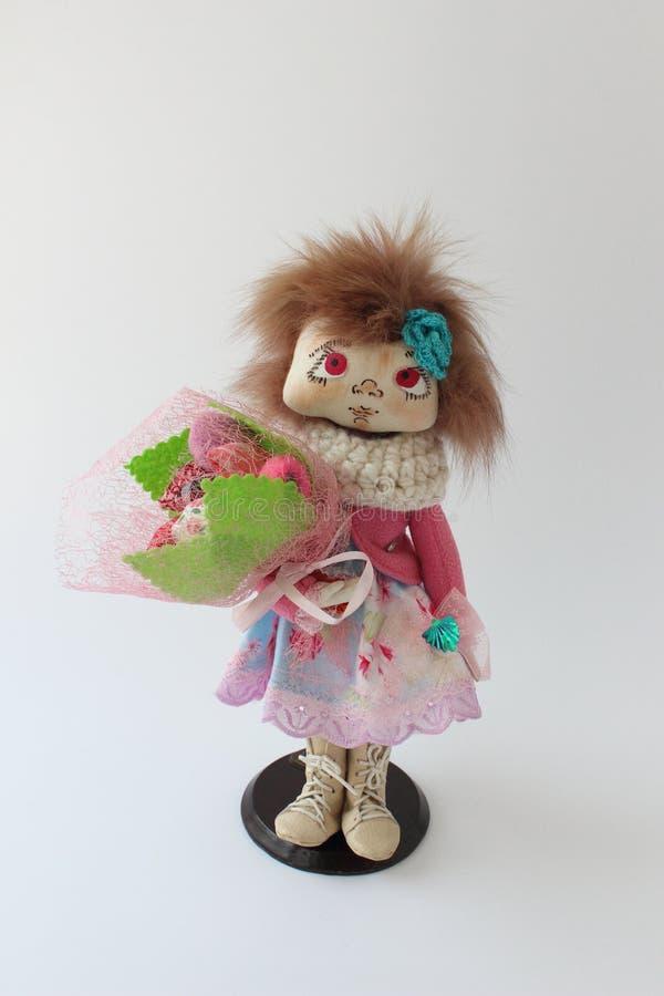 Poupée de textile dans une veste rose avec un bouquet des fleurs photos stock