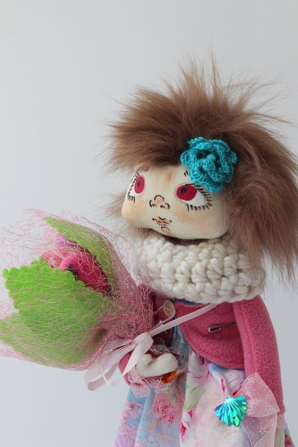 Poupée de textile dans une veste rose avec un bouquet des fleurs photo libre de droits