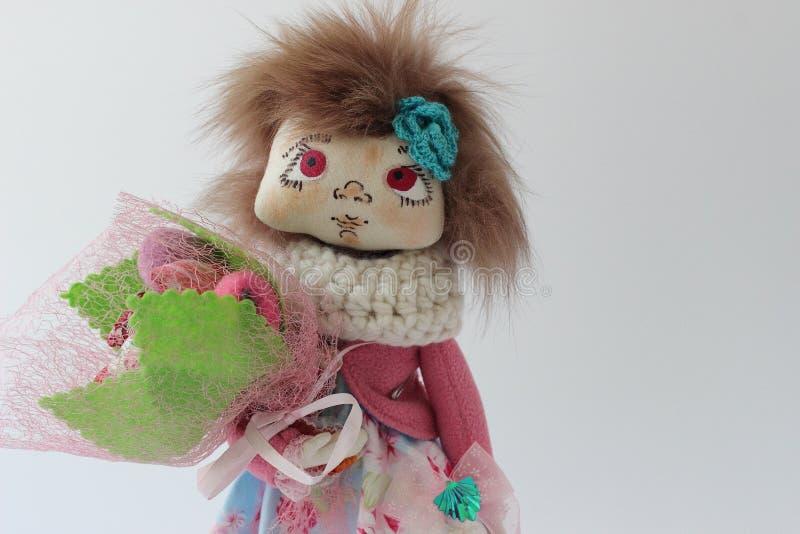 Poupée de textile dans une veste rose avec un bouquet des fleurs photo stock