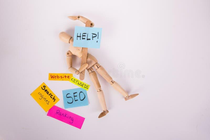 Poupée en bois jointe fixant tenant des mots-clés collants de sites Web d'un rang des notes SEO de signe de piquet d'aide photos stock