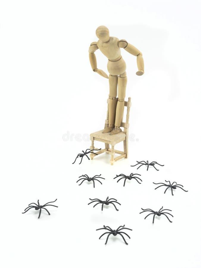 Poupée en bois téléchargée pour présider avec la phobie d'araignée photo libre de droits