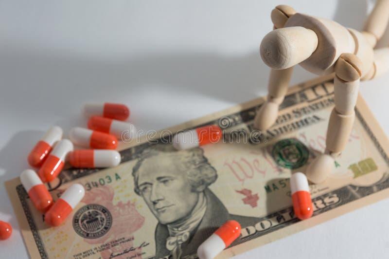 Poupée jointe en bois se mettant à genoux vers le bas et pilule sur le dollar photo stock