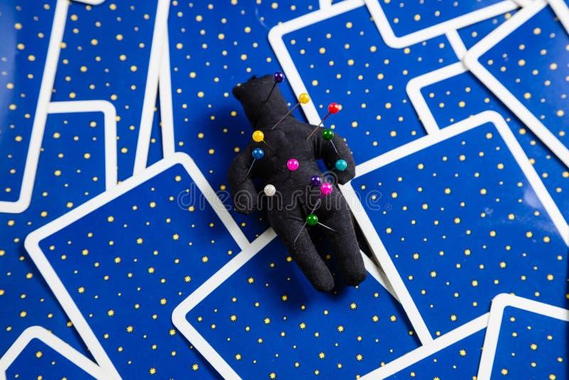 Poupée noire de vaudou sur un fond des cartes de tarot. images stock