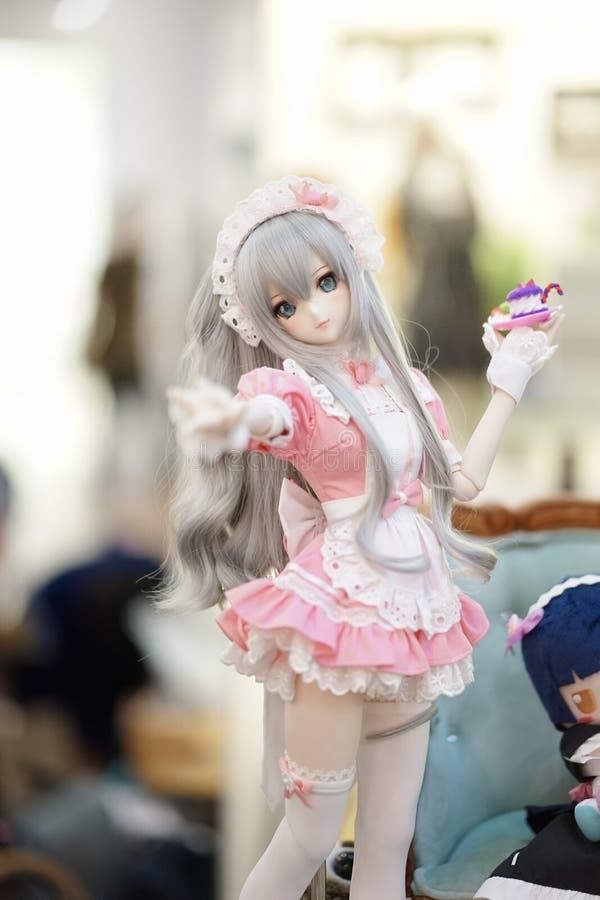 Poup?e mignonne sur l'affichage Une photo de portrait d'une fille de domestique portant un uniforme rose de domestique dans le st images libres de droits