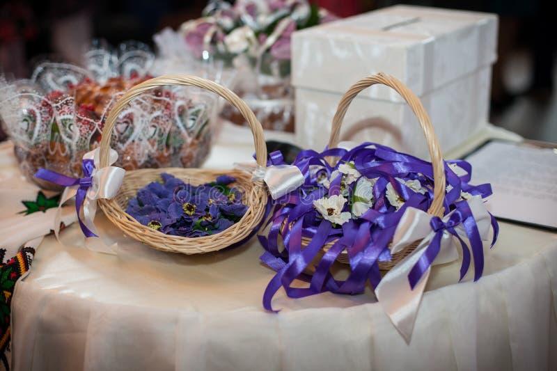 Pouporri und Blumen mit Bändern in den rustikalen Körben als Hochzeitsdekorationen an der Aufnahme lizenzfreies stockbild