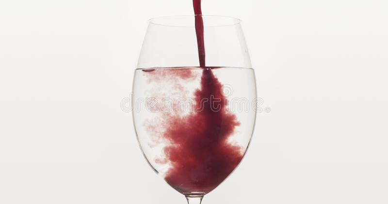 Pour blueberry juice into water in wine glass royalty free stock photos