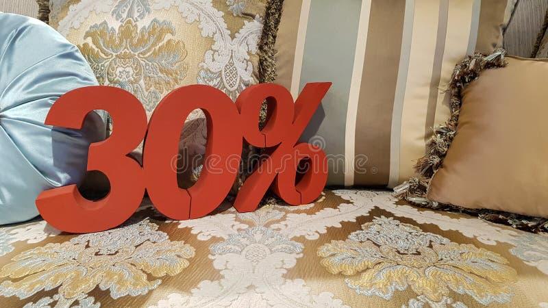 Pour cent de vente de promotion de remise des couleurs rouges 30% sur le sofa de tapisserie avec l'oreiller bleu dans le magasin, images stock