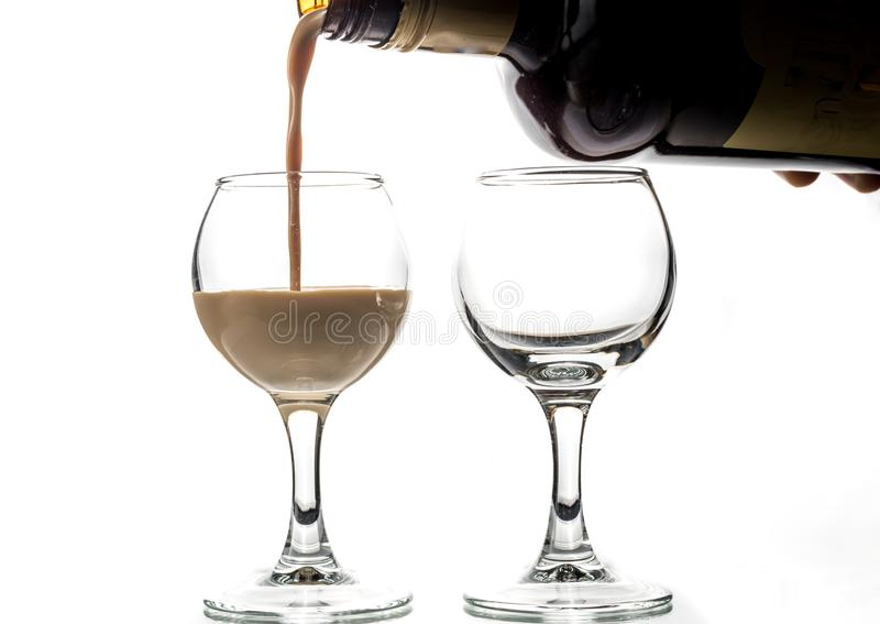Pour chocolate thick liquor in two round glasses.  royalty free stock image