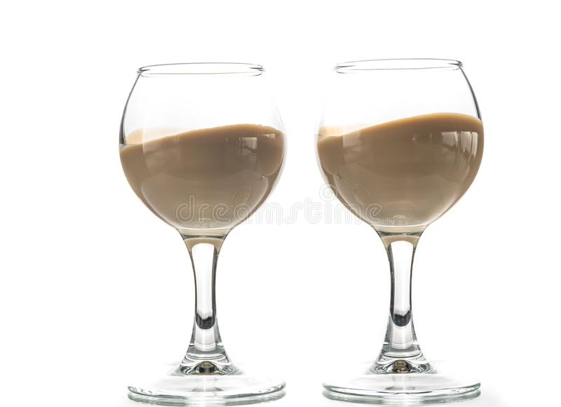 Pour chocolate thick liquor in two round glasses.  royalty free stock photo