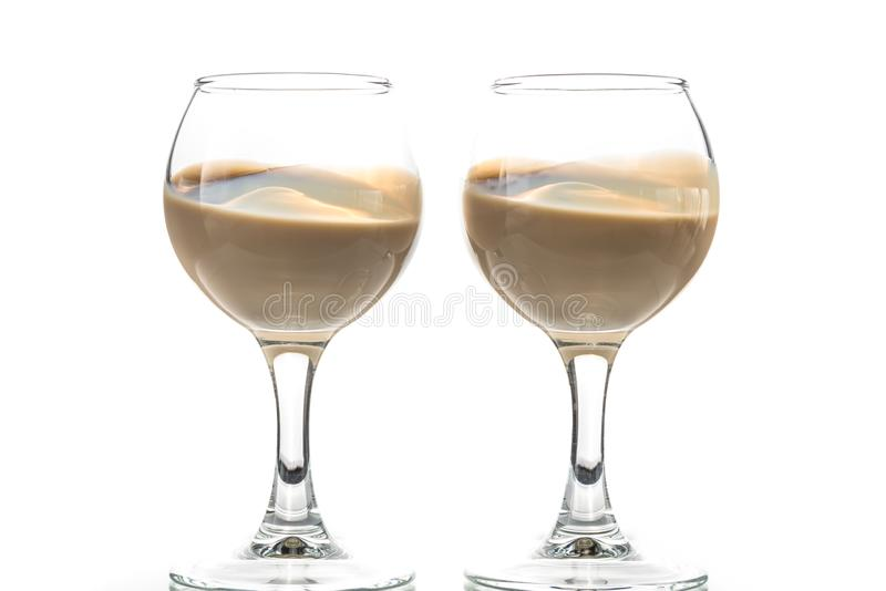 Pour chocolate thick liquor in two round glasses.  royalty free stock photography