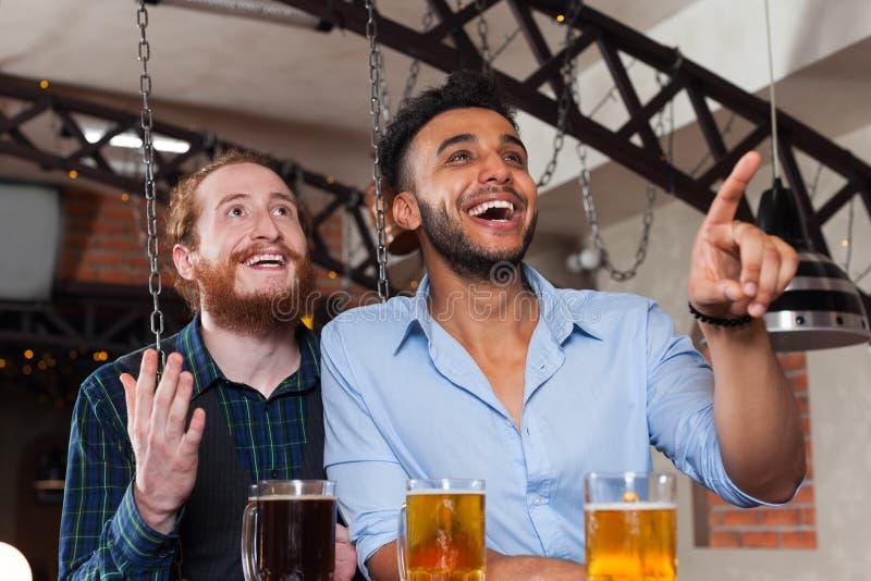 Pour deux hommes dans le football de observation de barre, bière potable se tenant au contre- doigt de point, amis gais de course images stock