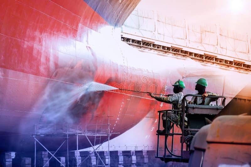Pour deux hommes nettoyant le fond d'un voilier avec le jet d'eau à haute pression images stock