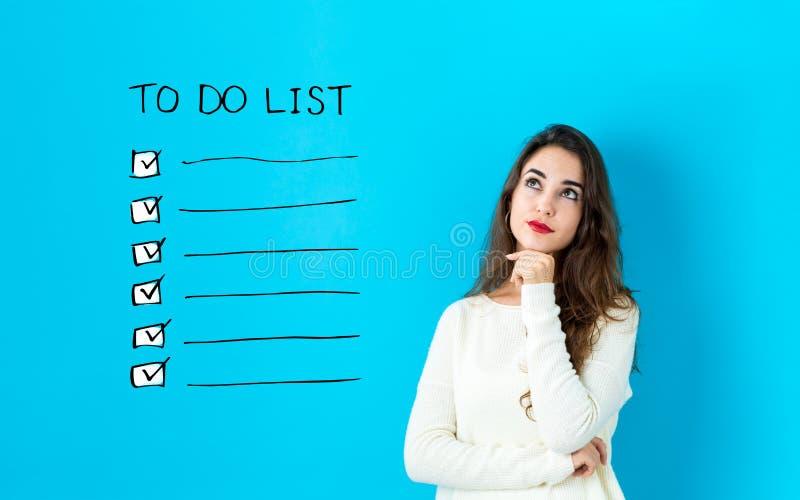 Pour faire la liste avec la jeune femme image stock