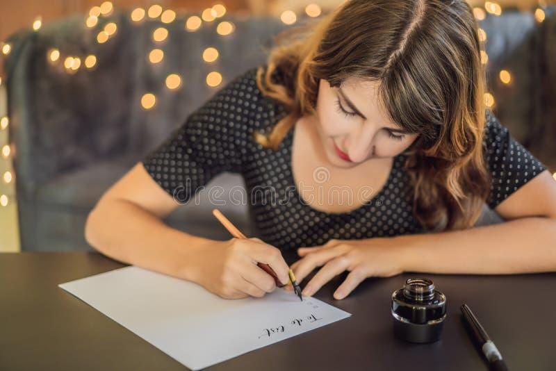 Pour faire le calligraphe Young Woman de liste écrit l'expression sur le livre blanc Inscrire les lettres d?cor?es ornementales c images stock