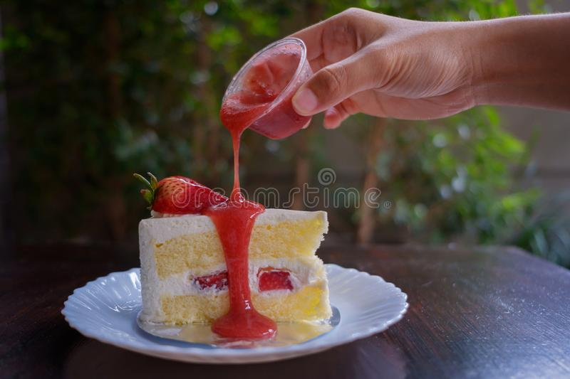 Pour the jam on the cake. royalty free stock photography
