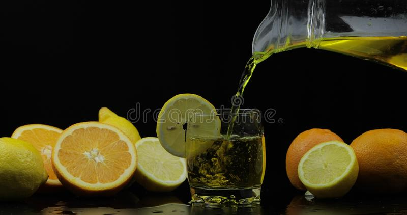 Pour juice from pitcher into glass, orange and lemon slices on background stock photography