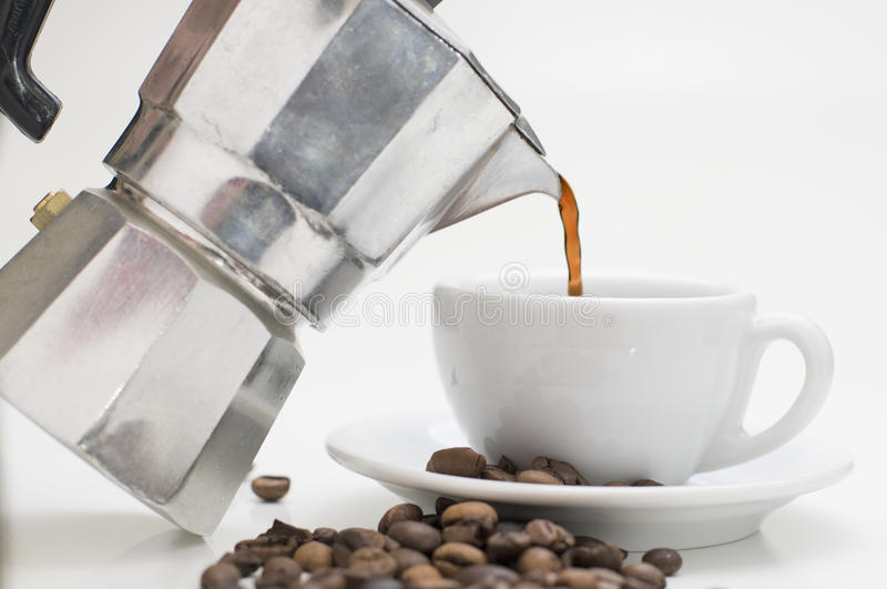 Pour out the coffee. Espresso pour in the espresso cup with coffee beans on the white background royalty free stock images