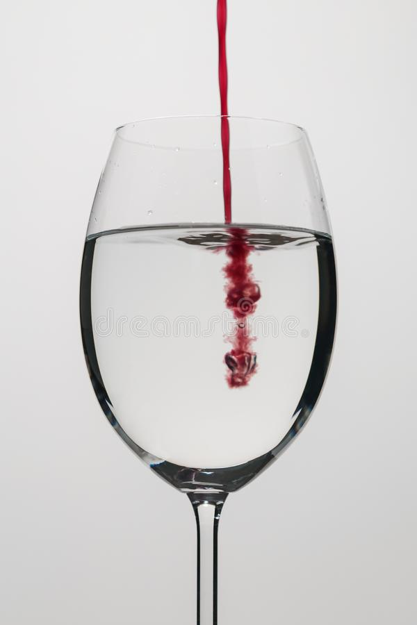 Pour purple juice into still water in wine glass. Closeup stock photo