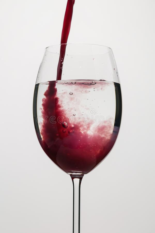 Pour purple juice into still water in wine glass. Closeup royalty free stock photo