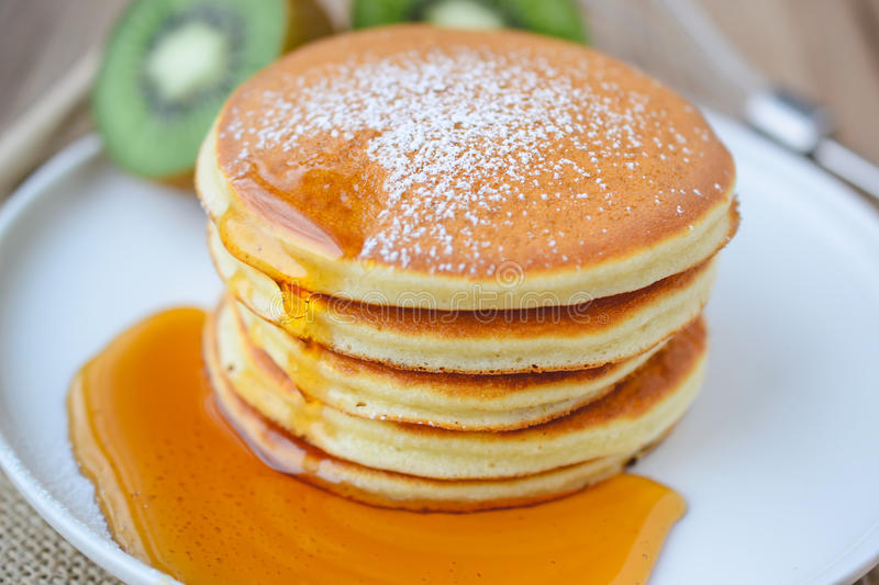 Pour syrup on stack of pancake on white plate and sackcloth with. Kiwi slices on wood background royalty free stock photography