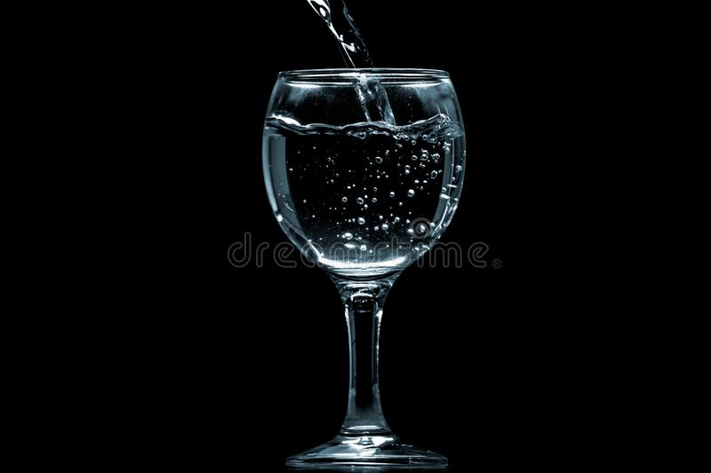 Pour water into glass on black background stock images