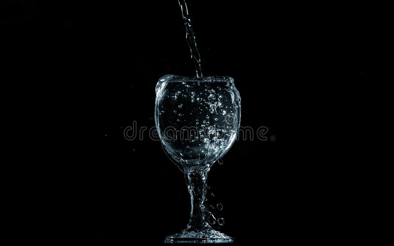 Pour water into glass on black background royalty free stock images