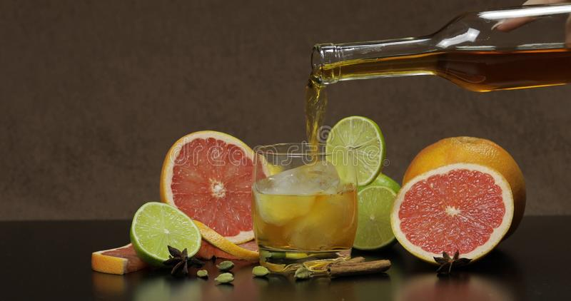 Pour whiskey, cognac, liqueur from a bottle into a glass cup. Pour liquor from a bottle into a glass cup with ice cubes. Fresh fruits in the background. Lime stock image
