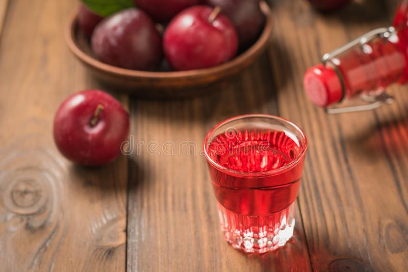 Poured a glass of plum liqueur, a bottle and ripe berries on a wooden table. Homemade alcoholic drink made from berries plum. The view from the top royalty free stock images