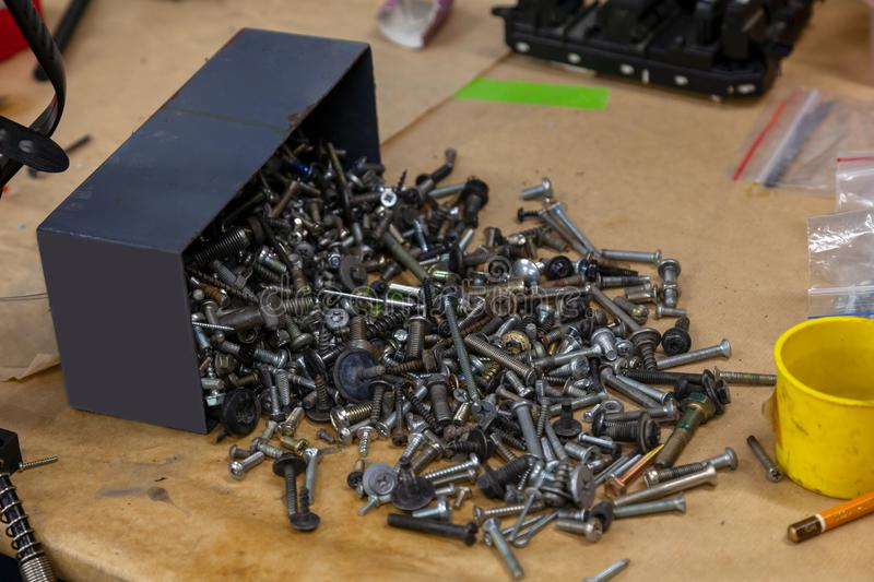 Poured out of the blue box parts: iron nuts screws and bolts on the table in the workshop royalty free stock photos