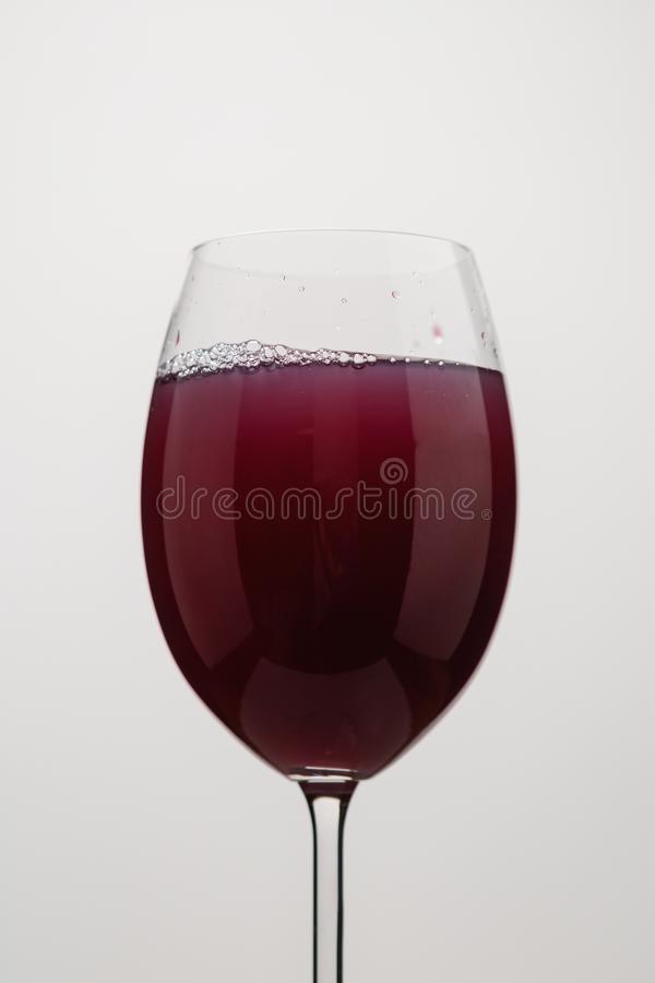 Poured purple juice into still water in wine glass. Closeup stock image