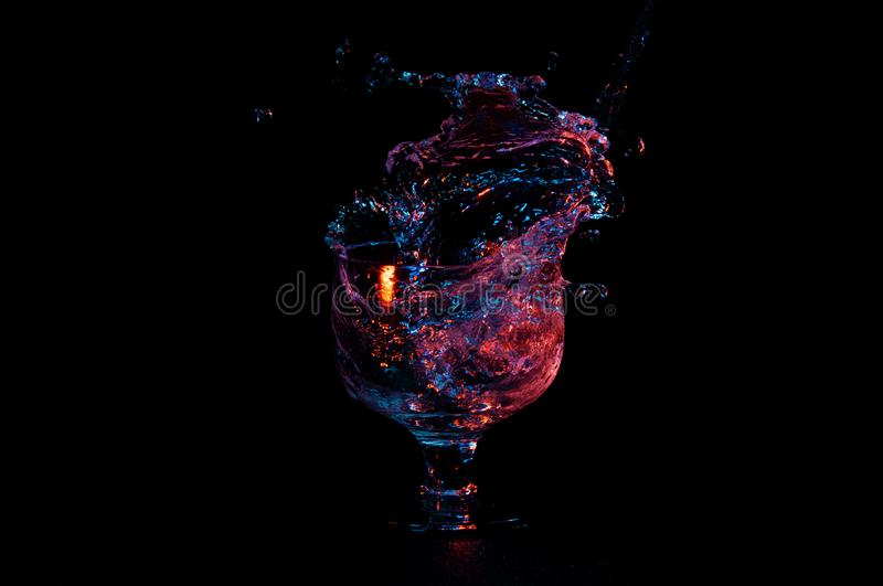 Water in vibrant colors splashing out of a glass stock images