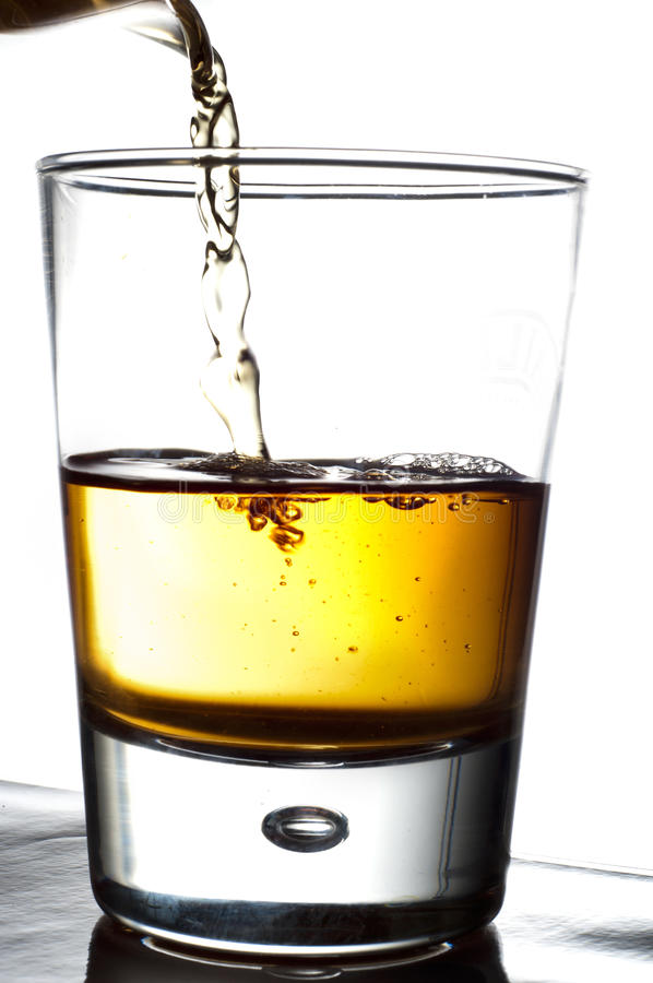 Pouring alcohol in a glass stock image