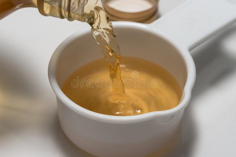 Pouring Apple Cider Vinegar into a Measuring Cup royalty free stock photos