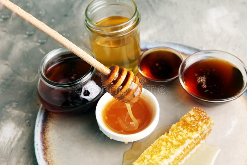 Pouring aromatic honey into jar, closeup royalty free stock image