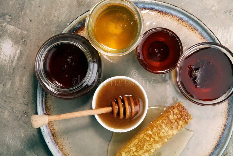 Pouring aromatic honey into jar, closeup. Pouring aromatic honey into jar with a honey dipper and a Honeycomb royalty free stock photos