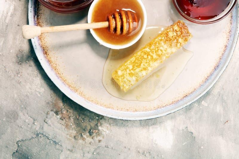 Pouring aromatic honey into jar, closeup. Pouring aromatic honey into jar with a honey dipper and a Honeycomb stock photos
