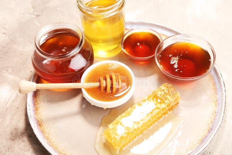 Pouring aromatic honey into jar, closeup. Pouring aromatic honey into jar with a honey dipper and a Honeycomb stock image