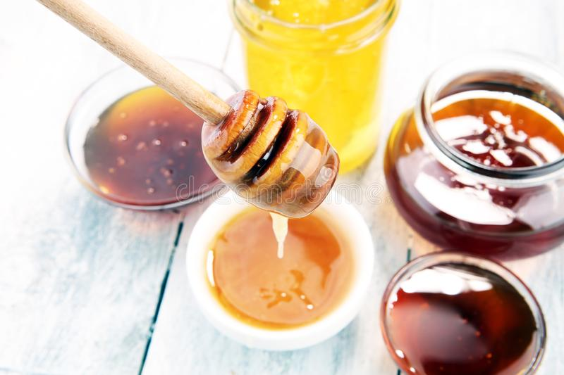 Pouring aromatic honey into jar, closeup. Pouring aromatic honey into jar with a honey dipper and a Honeycomb royalty free stock image